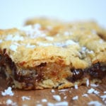 Coconut Chocolate Gooey Slice. This is a gooey cookie bar type slice filled with chocolate chips and coconut and thrown completely over-the-top with chopped Bounty Bars! #bountybarslice #coconutchocolatebars #cookiebars